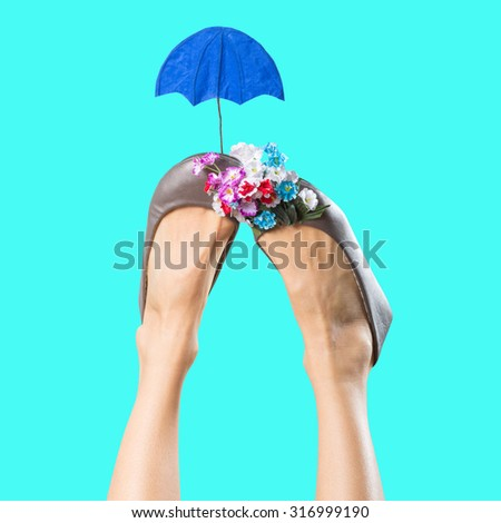 Fashionable woman legs with funny umbrella over blue background - stock photo