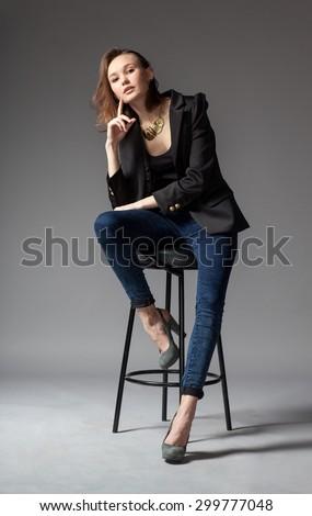 fashionable woman-model posing on the chair, studio photography - stock photo