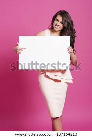 Fashionable woman pointing at empty whiteboard