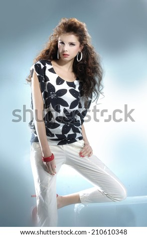 fashionable woman posing near the cube on gray background - stock photo