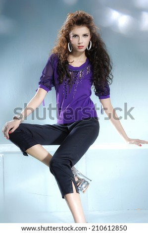 fashionable woman sitting posing in light background - stock photo