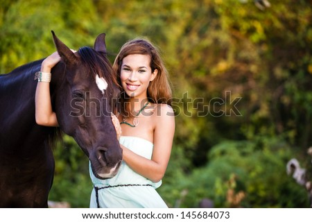 Fashionable woman with a horse in the countryside