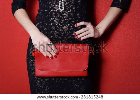 Fashionable woman with a red bag in her hands and black evening dress - stock photo