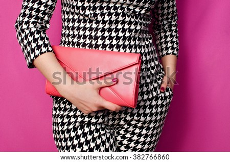 Fashionable woman with a red handbag in her hands and black white evening costume - stock photo