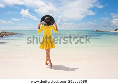 Fashionable woman with black summer hat and yellow dress on the beach - stock photo