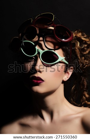 Fashionable woman with curly hair in many eyeglasses