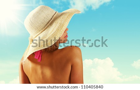 Fashionable woman with straw hat protects from sun - stock photo