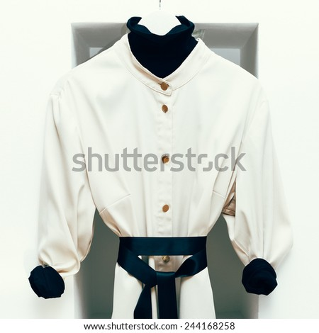 Fashionable women's coat in white interior. Black and white combination in clothing.