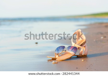 Fashionable women sandals and sunglasses on summer sandy wet coastline. Outdoors image. - stock photo