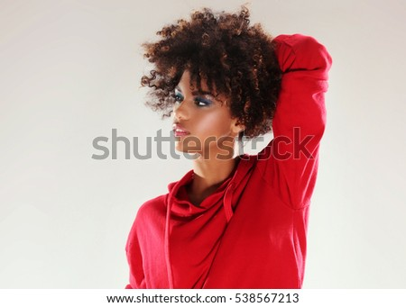 Fashionable young african american girl with afro in red blouse and jeans posing in studio.