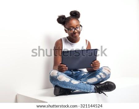 Fashionable young african american teenage girl using tablet. Girl wearing eyeglasses. Studio shot. - stock photo