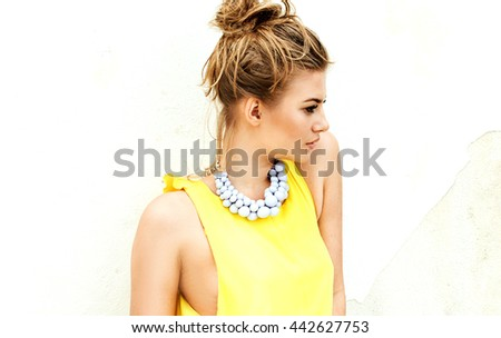 Fashionable young attractive woman in yellow dress. Summer photo. Sunny day.