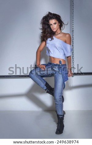 Fashionable young beautiful brunette woman posing in studio, looking at camera. - stock photo
