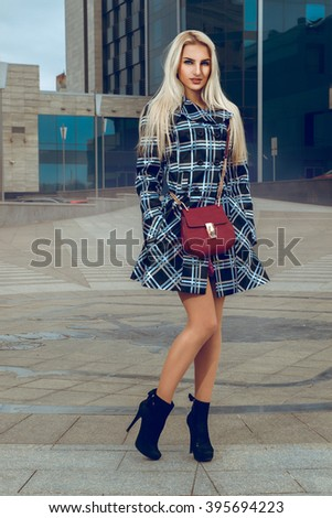 Fashionable young blond model in coat looking at the camera outdoors. fashion model posing outdoors. fashionable and glamour concept.