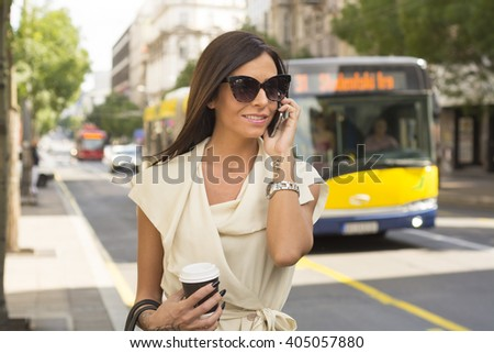 Fashionable young brunette wearing white dress and sunglasses laughs into phone on street, city, urban space - stock photo