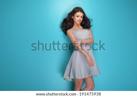 Fashionable young brunette woman posing in studio, looking at camera. Girl with long curly hair. - stock photo