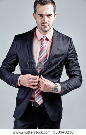Fashionable young businessman closing his jacket isolated over grey - stock photo