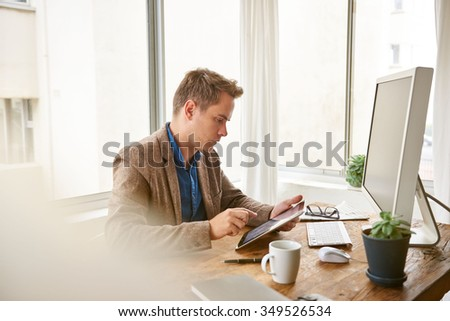Fashionable young businessman using his digital tablet at his neat and contemporary office desk - stock photo