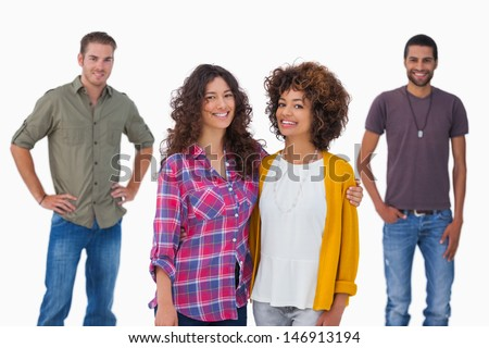 Fashionable young friends smiling at camera on white background - stock photo