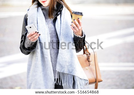 Fashionable young hipster woman in trendy oufit is looking her mobile with a smile on her face. City life background.