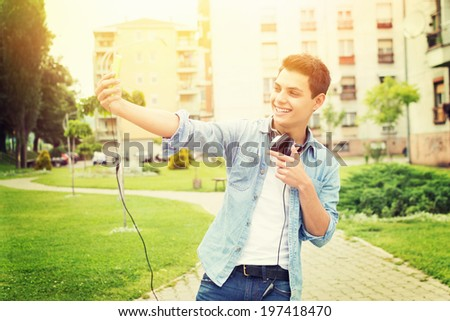 Fashionable young Hispanic hipster man taking a selfie with smart phone outdoors in park on sunny summer day. Modern lifestyle concept. - stock photo