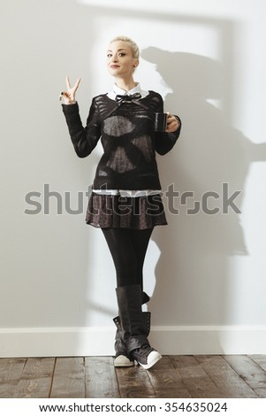 fashionable young lady with a cup coffee in an empty room