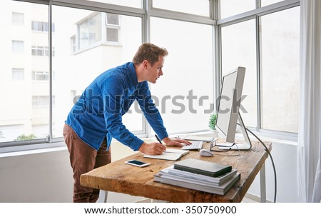 Fashionable young male entrepreneur standing at his desk and writing notes in his journal while looking at something on the screen of his computer - stock photo