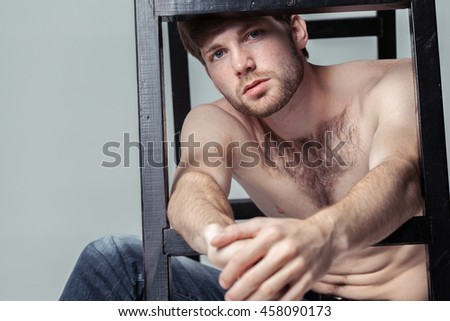 fashionable young man posing with a ladder in studio