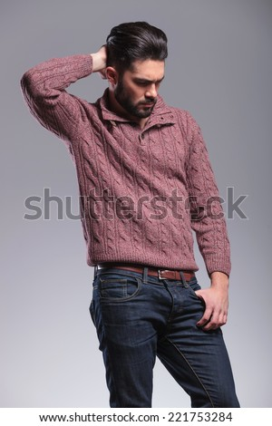 Fashionable young man with beard, fixing his hair while holding his thumb in his pocket. Side view, looking down. - stock photo