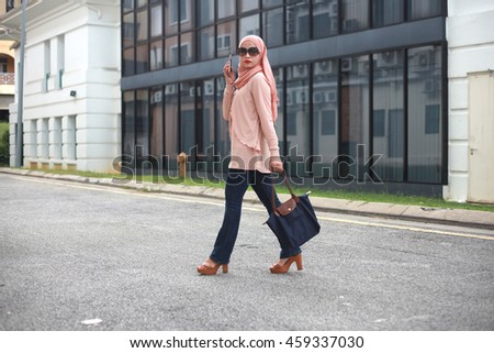 Fashionable Young Muslim Woman in Beautiful Hijab Busy Calling with her Mobile Phone While Walking Across a City Street