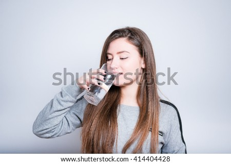 Fashionable young woman drinking a glass of water, close-up isolated on a gray background