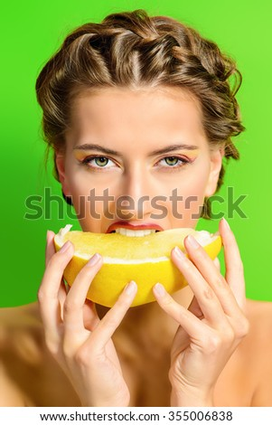 Fashionable young woman eating pomelo over green background. Tropical fruits.  Healthy eating. Beauty, cosmetics.