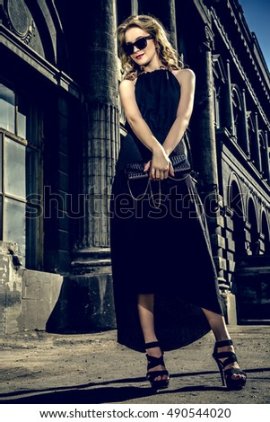 Fashionable young woman in a city center. Beautiful blonde girl in long black dress.