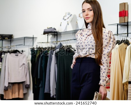 Fashionable young woman in a fashion showroom - stock photo