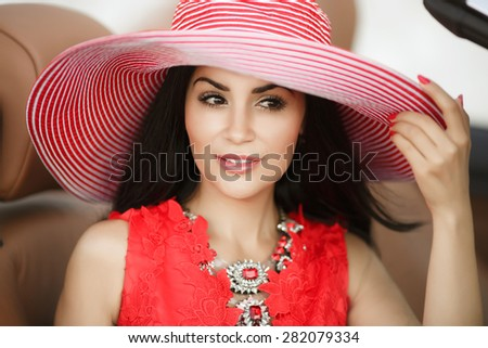 Fashionable young woman in car smiling girl in hat summer portrait beautiful female in red dress outdoors, sexy fashion woman model in luxury car, soft focus, series - stock photo