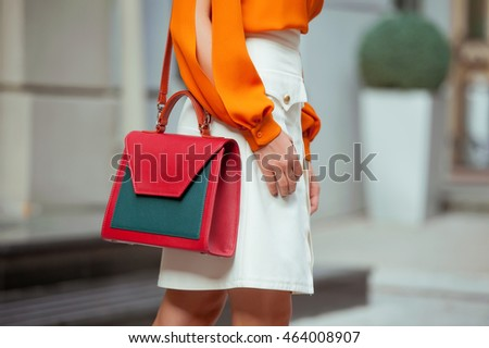 Fashionable young woman in orange blouse and white skirt with colorful handbag in hand on the city streets. Fashion.