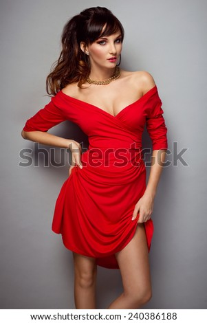 fashionable young woman in sexy red dress and nice hairstyle. Glamour girl - stock photo