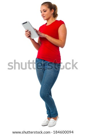Fashionable young woman operating her tablet pc - stock photo