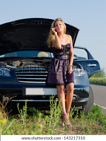 Fashionable young woman phoning for help on her mobile as she leans against her car which has broken down in the countryside - stock photo