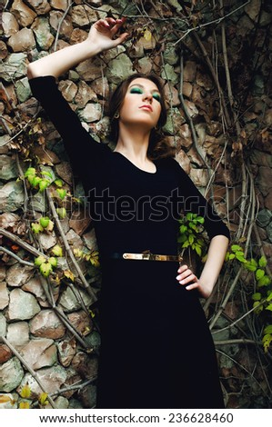 Fashionable young woman posing near a stone wall