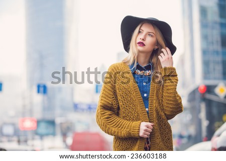 fashionable young woman posing outside in a city street - stock photo