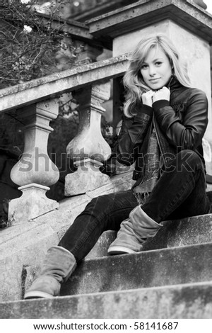 Fashionable Young Woman Sat On Steps - stock photo