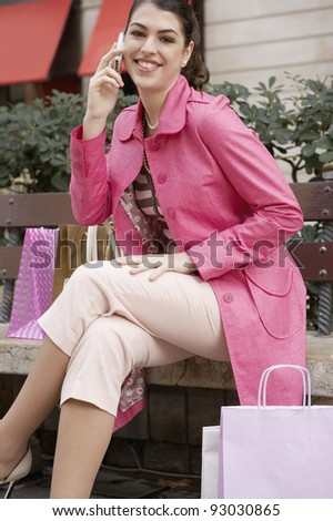 Fashionable young woman sitting down on a bench in a shopping street, using a cell phone. - stock photo