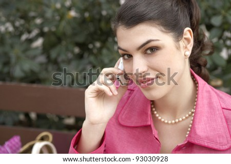 Fashionable young woman sitting down on a bench, using a cell phone.