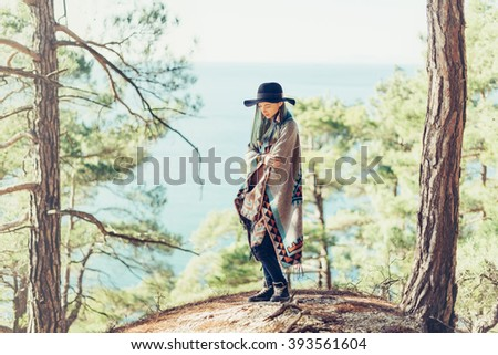 Fashionable young woman wearing in hat and poncho standing on coast in the forest among pine trees on background of sea
