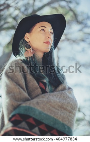 Fashionable young woman wearing in poncho and hat walking outdoor