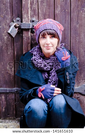 fashionable young woman wearing violet hat, scarf and original gloves - stock photo