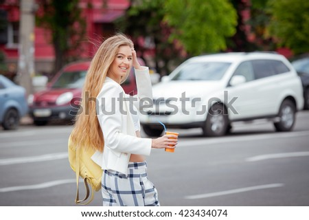 Fashionable young woman with a cup of coffee on the streets. Blonde woman with long hair. - stock photo