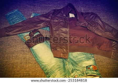Fashionable youth clothes: jeans, leather jacket, leather belt. Photo toned in yellow and purple. - stock photo
