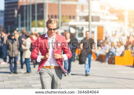 Fashioned young man in Oslo walking on crowded sidewalk with people on background. He has nordic facial features, and wearing a red jacket with gray trousers